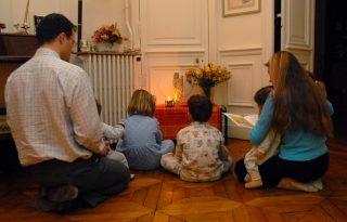 Février 2007: prière en famille à la maison. Parents priant avec leurs enfants devant l'oratoire familial (catholicisme) France.