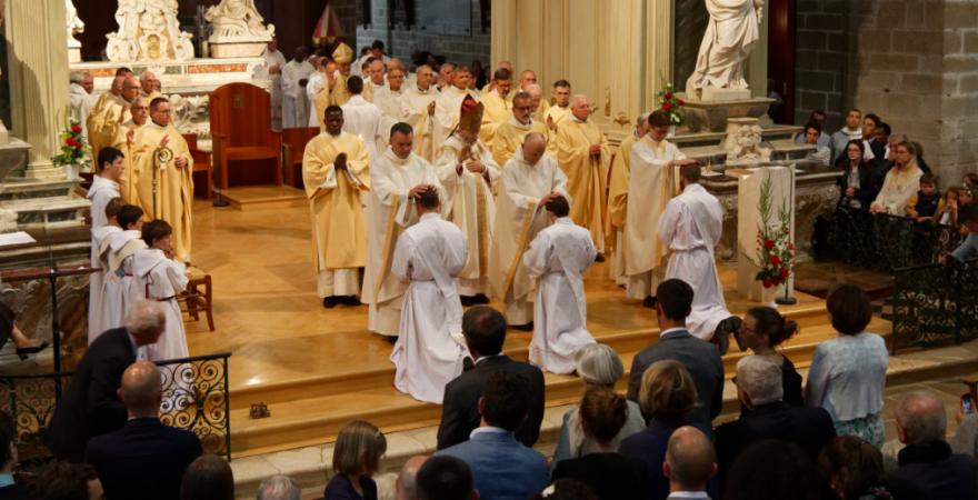 Imposition des mains par les prêtres présents à la suite de l'Evêque, sur les ordinands à genoux