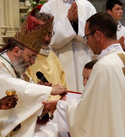 Avec le saint Chrême, l'Evêque oint les paumes des mains des nouveaux prêtres
